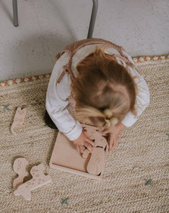 A child playing with wooden stacking puzzle.