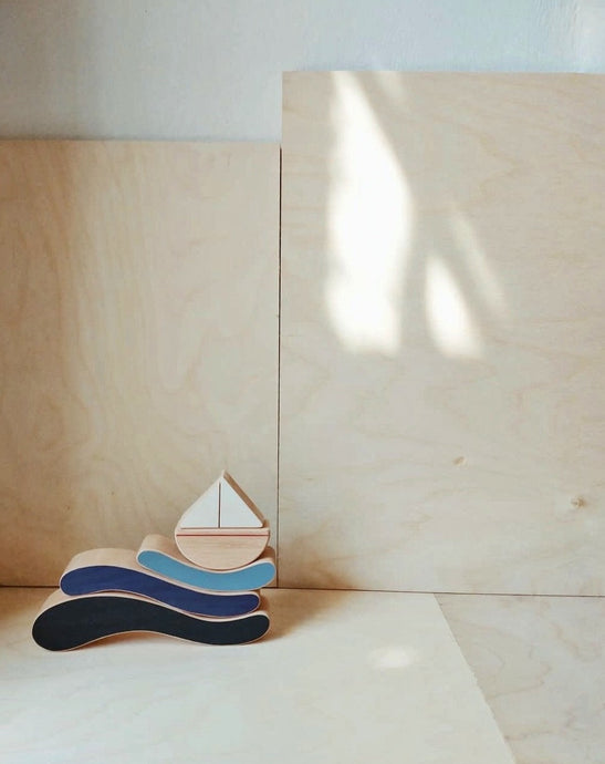 Wooden sailboat balancing on wooden waves.