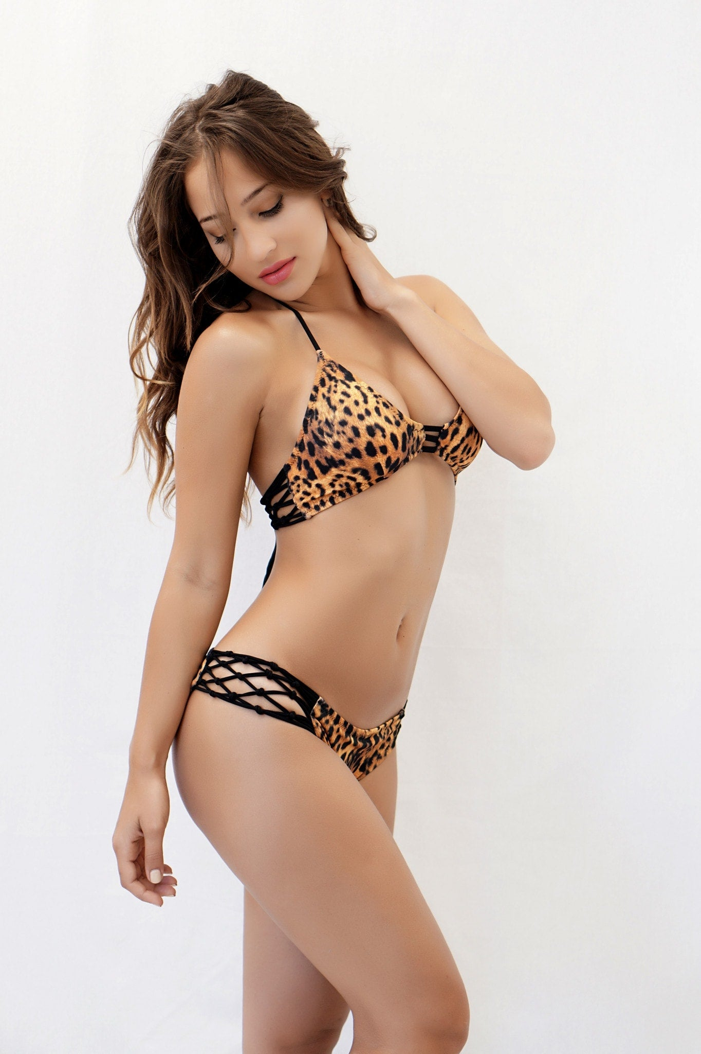 Look fiercely sexy in this leopard print bikini featuring small triangle cups, clear halter straps, clear underbust straps with a tie back closure, and matching micro bottoms with clear straps and thong back.