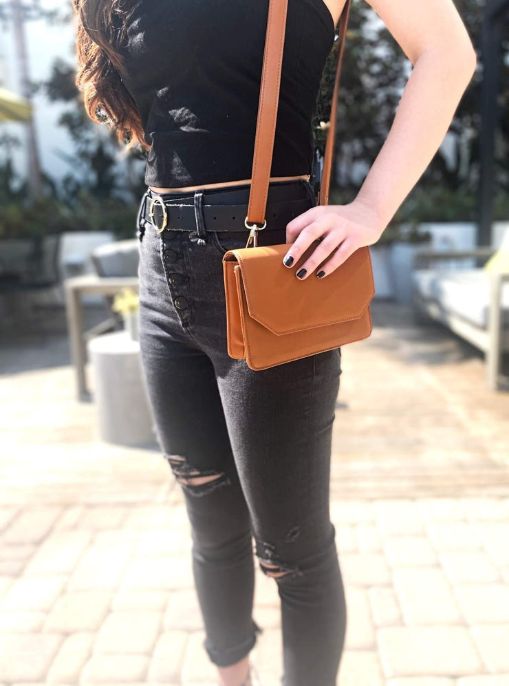 Our brown sustainable vegan leather convertible quarantine bag worn as a shoulder bag. The perfect bag for quarantine, for your masks, hand sanitizer, bag on the go. Good for fashion and sustainability.