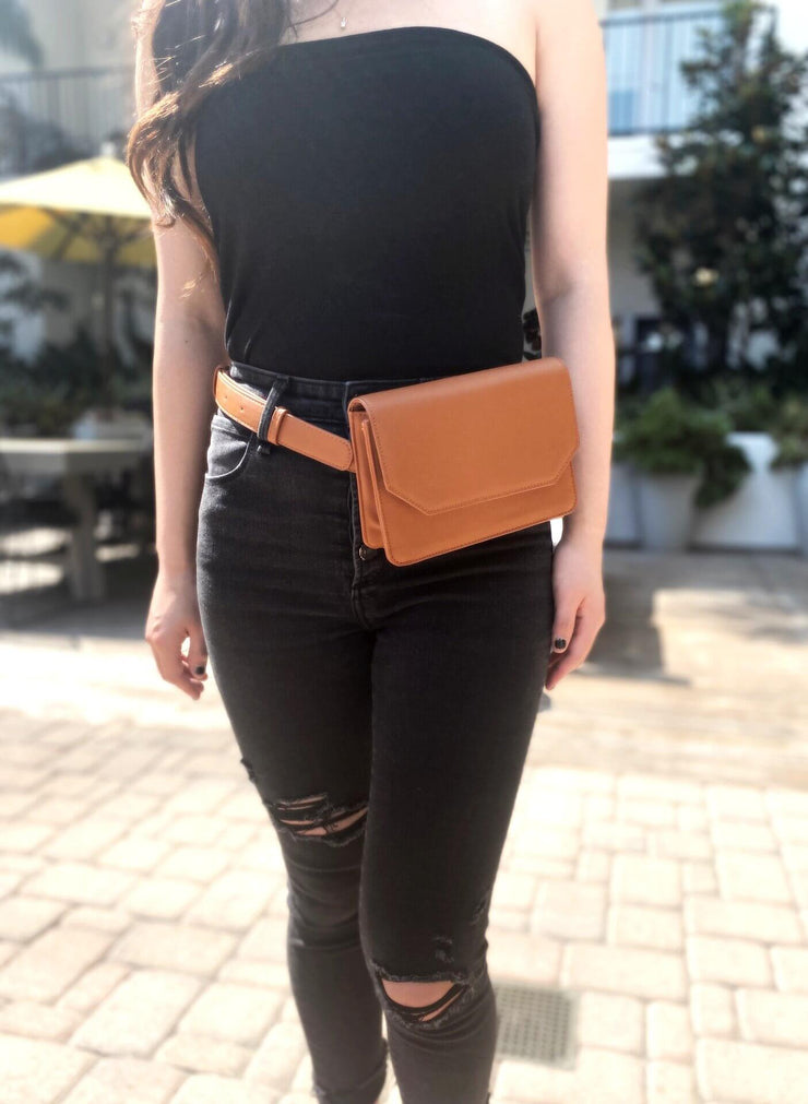 Our brown sustainable vegan leather convertible quarantine bag worn as a belt bag. The perfect bag for quarantine, for your masks, hand sanitizer, bag on the go.