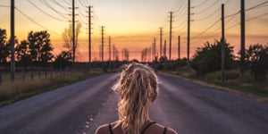 woman on road looking at utility poles and power lines