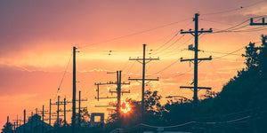 power poles and power lines during sunset