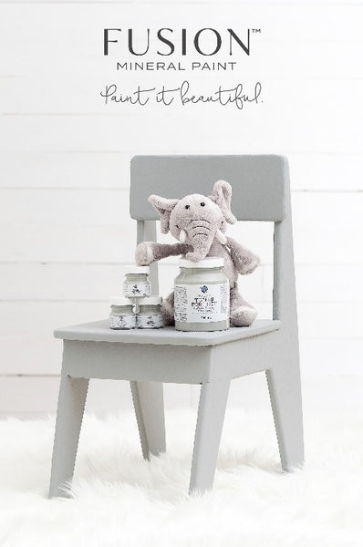 Fusion Mineral Paint | Chair painted with little lamb painting with decor against a white wall with white fuzz on the floor.