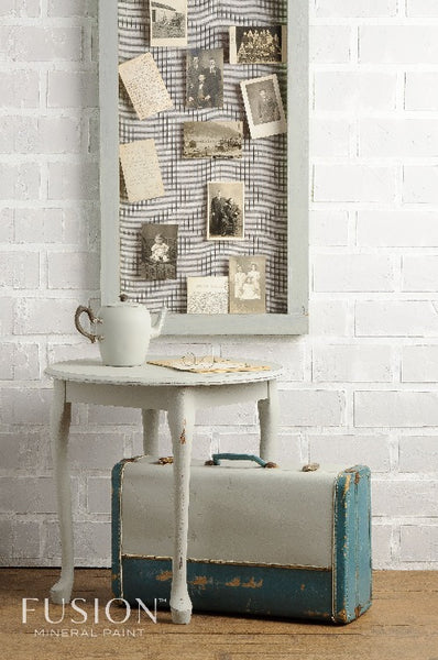 Fusion Mineral Paint | Rustic themed photo with postcards hanging up on the white bring wall behind a table and briefcase with other decor