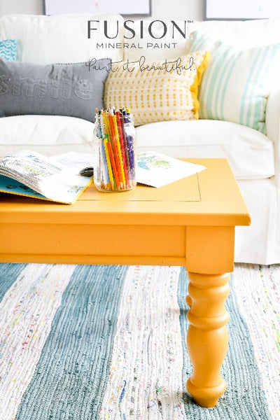 Fusion Mineral Paint | Mustard painted wooden table with pencils and colouring books on top of it in a living room setting.