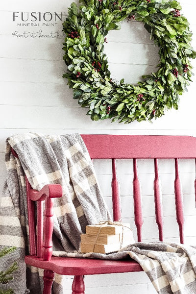 Fusion Mineral Paint | Wooden Bench painted with Cranberry with wreath hanging on the wall behind it and a blanket draped over the side.