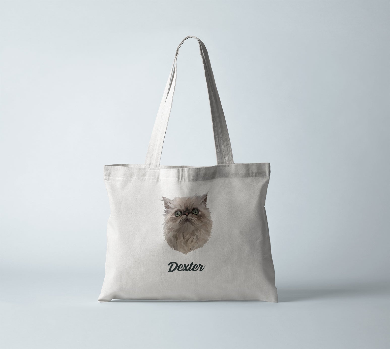 Canvas tote bag in bright white, with personalized pet portrait of a cat with its name in black.