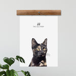 Load image into Gallery viewer, Custom hand illustrated pet portrait of a cat named JJ with custimized text underneath it's name. The cat portrait is printed on our Cloud White poster and hung up.