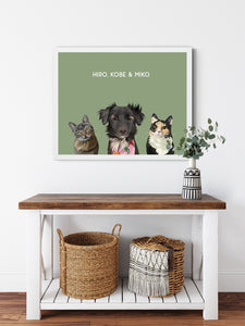 Trio custom framed pet portrait of a cat, dog and cat on sage green background with white frame. Personalized name of cat, dog and cat in white font.