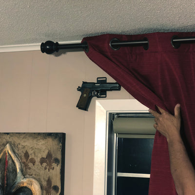 CoJo gun magnet holding over a window behind a curtain in a house.