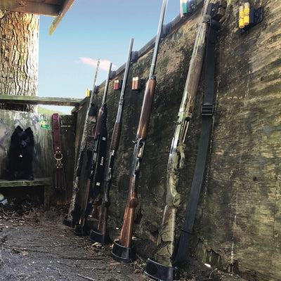 Six shotguns sitting in a Cojo Assperatus securing the but of the shotguns in a duck blind to prevent a gun accident.
