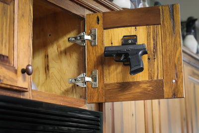 Cojo gun magnet holding a pistol in a kitchen cabinet.