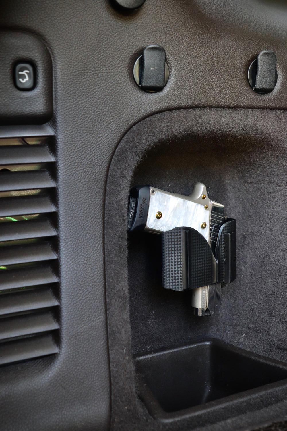 CoJo universal gun holster mounted in the side panel of a vehicle