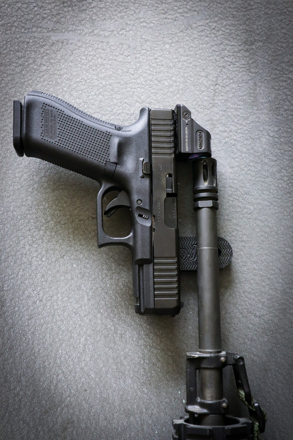 Pistol and a AR rifle held by a gun gripper gun magnet on a safe door