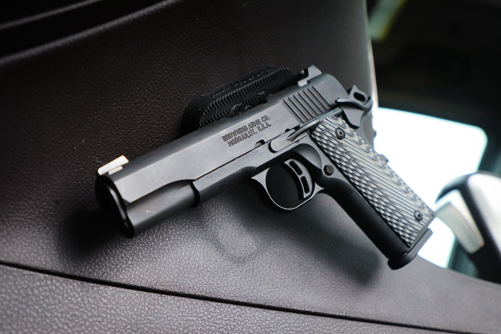 Semi Automatic pistol on a CoJo Gun Gripper mounted to the side of the console in a vehicle