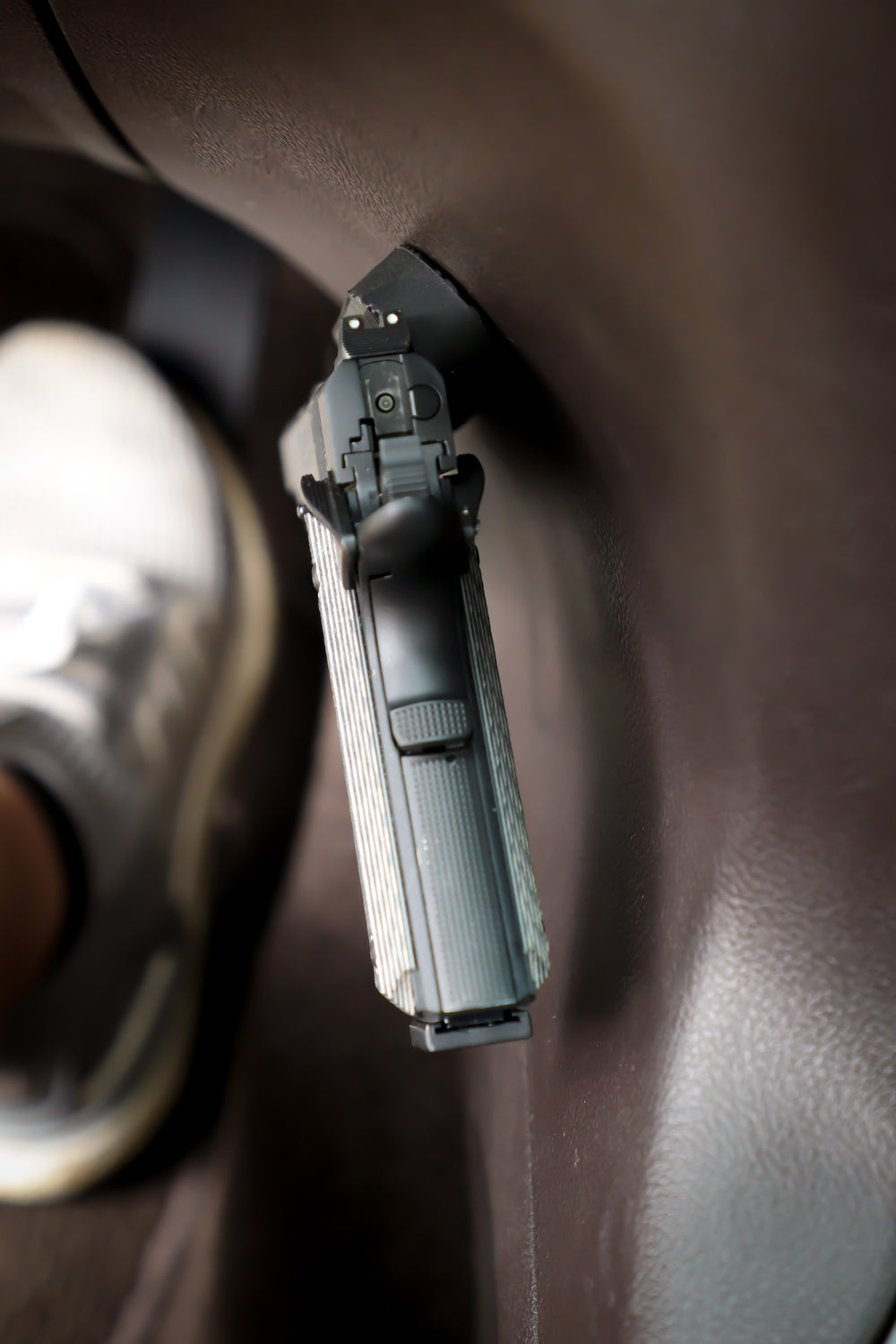 Picture of a Semi Automatic pistol from behind mounted on the side of the console of a vehicle.