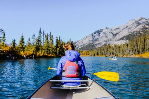 A woman in a blue jacket sitting in a canoe with a yellow paddle.