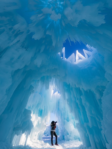 A photographer taking pictures inside an Alaskan glacier