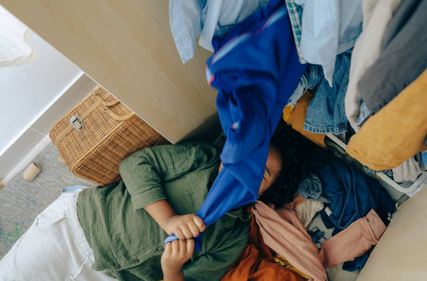 woman lying under a heap of used maternity clothes