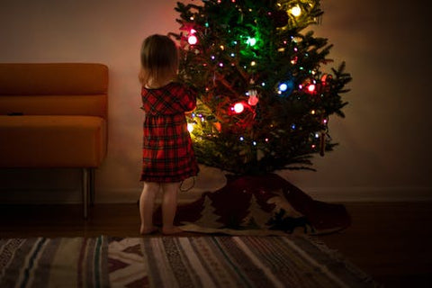 little girl in a christmas dress decorates the tree