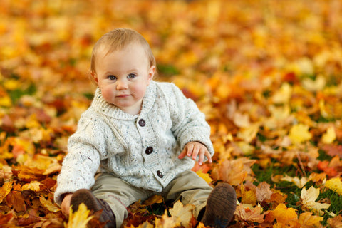 A baby boy wearing a cardigan sitting in a pile of autumn leaves
