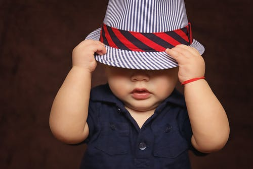 A baby boy wearing a navy top pulls a striped hat down over his eyes