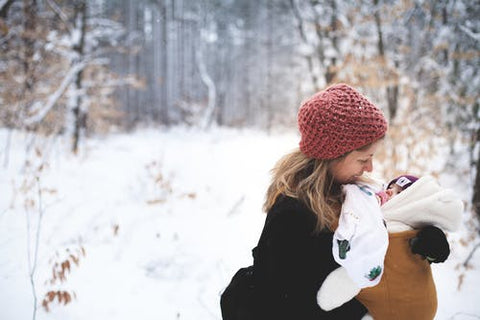 mother holds a baby in a snowsuit in the snow