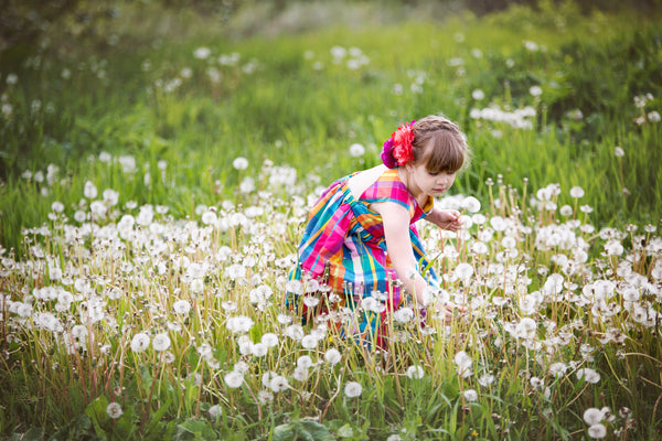 A young girl wearing a pink and blue dress is in a meadow of dandelion flowers