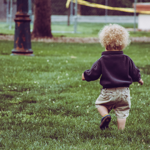 a toddler boy with blond curly hair walks through grass