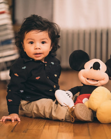 a young boy holding a Disney Mickey mouse toy