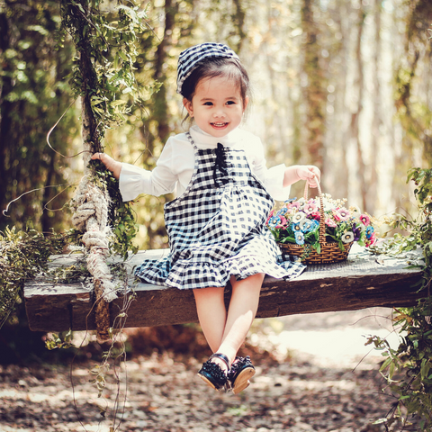 A preschool girl sitting on a wooden bench in a woodland wearing a checked dress and hat and carrying a basket of flowers