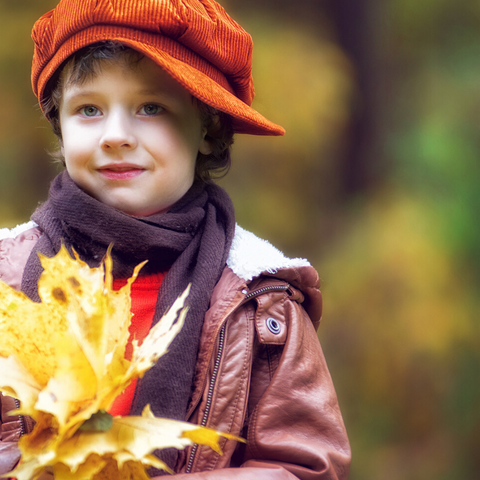 A young boy wearing an orange hat and a brown jacket and scarf holds some Autumn Leaves