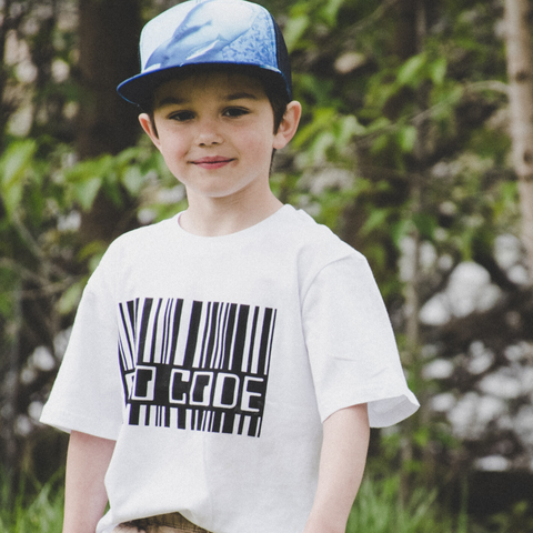 a Young boy wears a white t shirt and blue cap