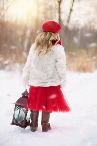 girl in the snow wearing christmas coat