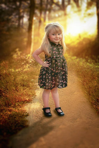 A young girl wearing a pretty floral dress stands on a pathway outside