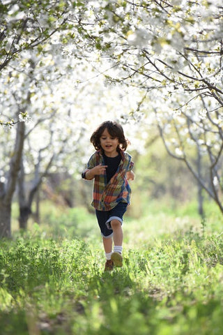 Younger boy walks through a meadow with trees filled with blossom