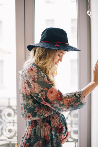 pregnant lady wearing used pregnancy clothes long sleeved floral dress and a hat