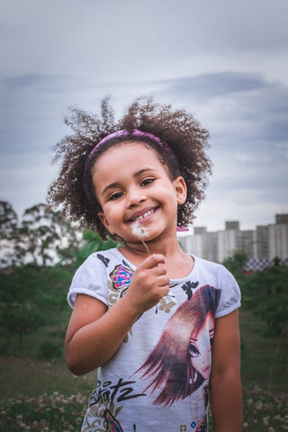 a young black girl smiles for the camera holding a dandelion