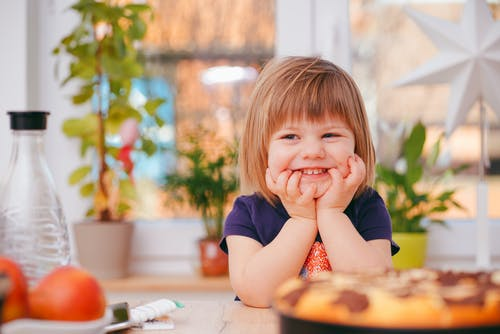 a toddler girl wearing a navy blue t-shirt is smiling sitting at a table surrounded by plants