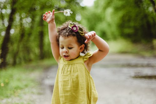 A toddler girl walking down a road wearing a yellow dress holds a dandelion above her head