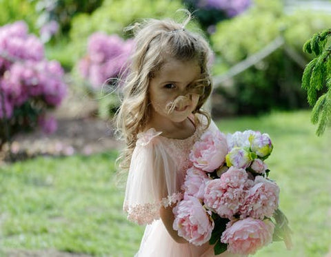 Girl holding a bunch of pink roses in a garden