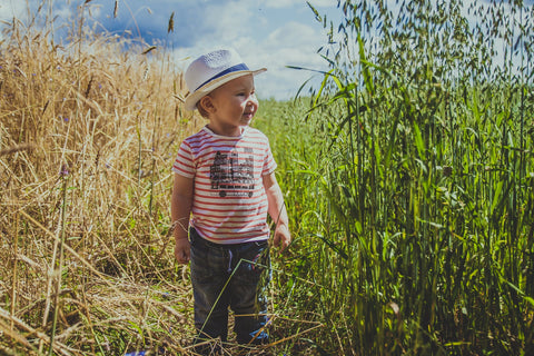 A Toddler Boy UK in field of corn wearing a striped t-shirt and hat