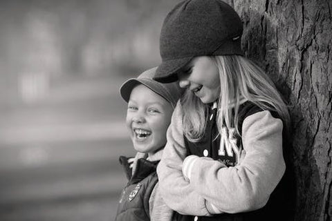 A boy and girl wearing unisex clothing in a black and white shot