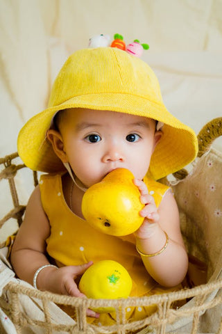 A baby sitting in a basket wearing yellow clothes and a hat and holding yellow fruit