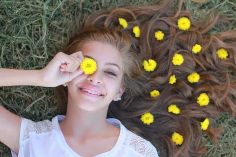 A teenage girl lies in grass with yellow flowers in her hair