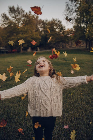 A girl wearing a beige jumper throws autumn leaves up into the air