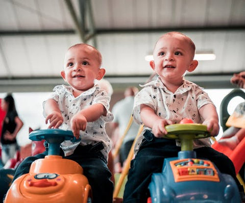 Twin Boys wearing identical outfits sit on toy cars