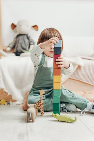 A young child in gender neutral clothes stacks a tower of blocks