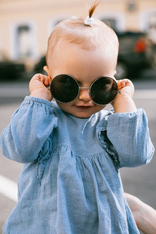 Fashionable toddler girl wearing a denim dress and holding sunglasses over her eyes